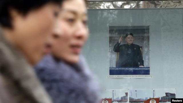 Women walk past a picture of the new North Korean leader Kim Jong-Un outside the North Korean Embassy in Beijing December 12, 2012.