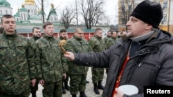 "An Orthodox priest blesses members of the newly created Ukrainian interior ministry battalion ""Saint Maria"" during a ceremony before they head to militay training, in front of St. Sophia Cathedral, in Kyiv, Feb. 3, 2015."