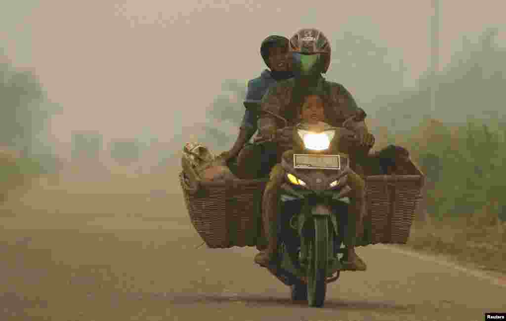 A family rides on a motorcycle as the haze hits Kubu district in Rokan Hilir, Indonesia, June 25, 2013.