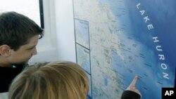 Estudiantes miran en un mapa del Lago Huron lugares donde hay buques hundidos en Thunder Bay National Marine Sanctuary.