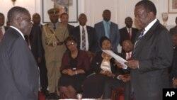 Emmerson Mnangagwa, right, is sworn in as vice president by Zimbabwean President Robert Mugabe at State House in Harare, Friday, Dec, 12, 2014. (AP Photo/Tsvangirayi Mukwazhi)