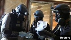 FILE - A U.N. chemical weapons expert, wearing a gas mask, holds a plastic bag containing samples from one of the sites of an alleged chemical weapons attack in the Ain Tarma neighborhood of Damascus, Syria, Aug. 29, 2013.