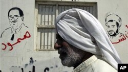 """A Bahraini man passes a wall bearing depictions of jailed Bahraini opposition figures Ebrahim Sharif (L), with the word """"steadfast"""" sprayed in red, and Sheik Mohamed Habib Moqdad (R), with the words """"We will never forget you"""" and above graffiti reading """"G"""