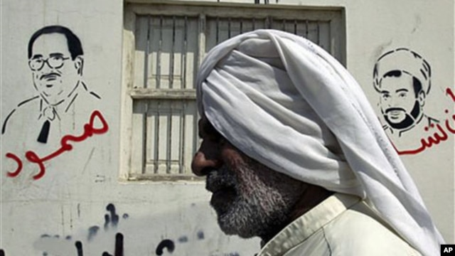 "A Bahraini man passes a wall bearing depictions of jailed Bahraini opposition figures Ebrahim Sharif (L), with the word ""steadfast"" sprayed in red, and Sheik Mohamed Habib Moqdad (R), with the words ""We will never forget you"" and above graffiti reading ""G"