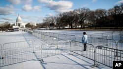 A pedestrian stands at the intersection of barricades dividing areas of standing room on the National Mall in Washington, Jan. 18, 2017, as preparations continue for Friday's presidential inauguration.
