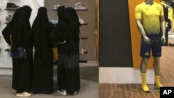 FILE - Saudi women shop at a mall in Riyadh, Saudi Arabia, Dec. 11, 2015. The kingdom has announced a projected budget deficit in 2016 as lower oil prices cut into the government's main source of revenue.