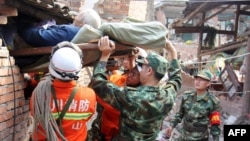 Rescuers carry a paralyzed elderly person from his damaged house in the city of Ya'an.