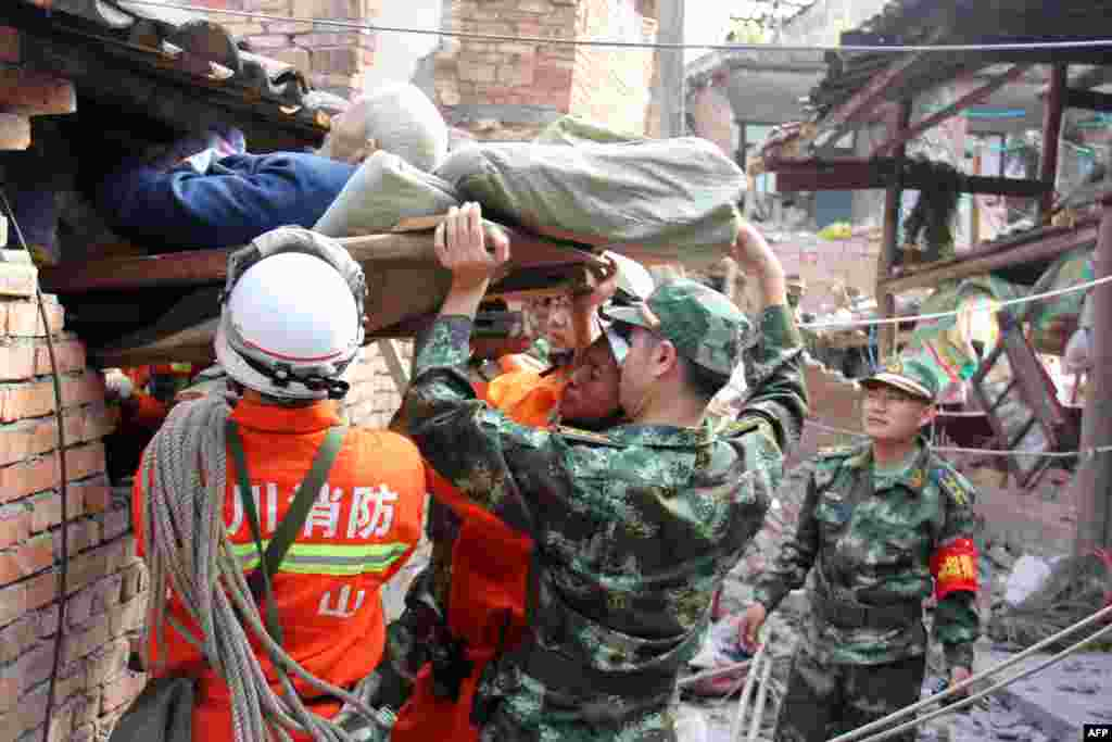 Rescuers carry a paralyzed elderly person from his damaged house in Qingren township in seriously damaged Lushan county after a shallow earthquake at magnitude 7.0 hit the city of Ya'an, in southwest China's Sichuan province.