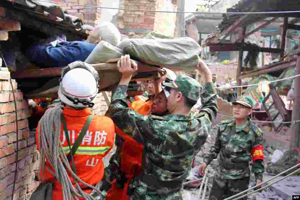 Những người cứu nạn khiêng một người lớn tuổi bị tê liệt ra khỏi ngôi nhà bị hư hại của ông tại thị trấn Tình Nhân Thảo thuộc huyện Lô Sơn, bị thiệt hại nặng sau trận động đất mạnh 7,0 độ Richter xảy ra tại thành phố Nhã Yên, tỉnh Tứ Xuyên, phía tây nam Trung Quốc.