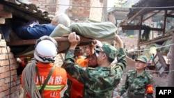 Les secouristes portant une personne âgée et handicapée depuis sa maison endommagée dans le canton de Qingren dans le comté de Lushan, après le puissant séisme - 20 avril 2013