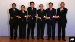 Japanese Prime Minister Shinzo Abe, third from left, join hands with leaders of the Mekong region nations.