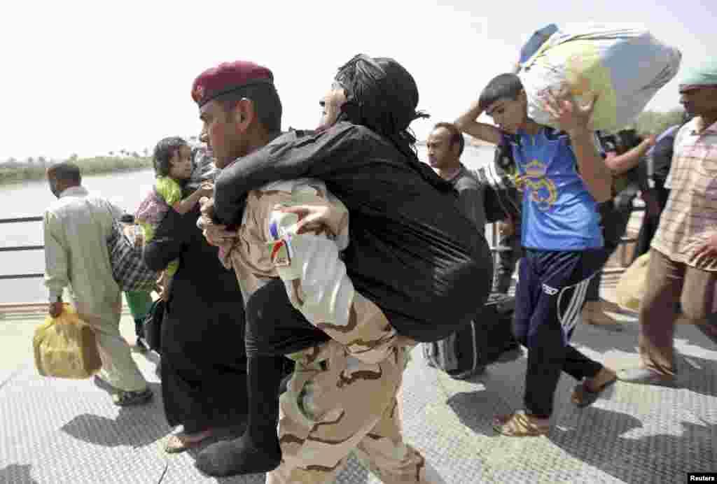 عراقی فورسز کا ایک اہلکار بوڑھی خاتون کو اٹھائے پل کے دوسری جانب لے کر جا رہا ہے۔