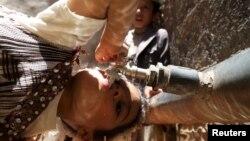 Seorang anak perempuan minum air dari keran di tengah-tengah krisis air bersih di Sanaa, Yaman, 24 April 2015. (Reuters/Mohamed al-Sayaghi)