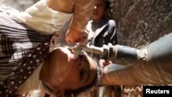 FILE - A girl drinks water from a faucet amid an acute shortage of clean drinking water in Sanaa, Yemen, April 24, 2015.