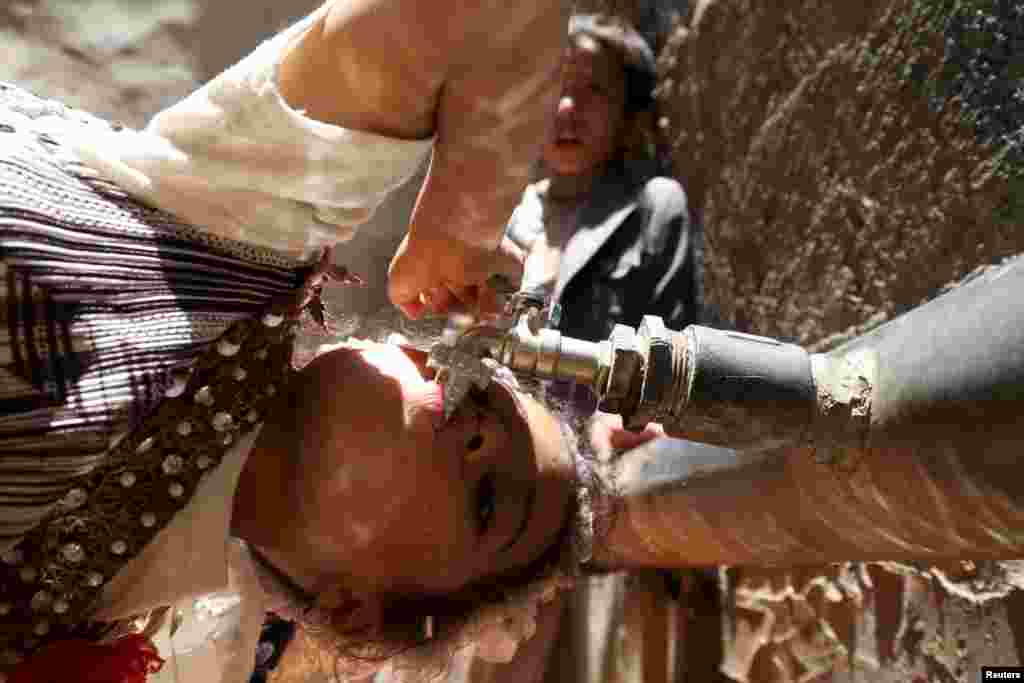 A girl drinks water from a faucet amid a major shortage of clean drinking water in Sanaa, Yemen.