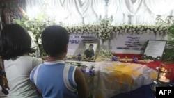 Reynalyn Dagsa (trái), và Andrew Dagsa, cầu nguyện trước quan tài của cha, ông Reynaldo Dagsa tại thành phố Caloocan ở phía bắc thủ đô Manila, ngày 4/1/2011