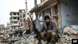 Seorang penembak jitu Kurdi Suriah duduk di antara puing-puing di kota Kobani, Suriah (30/1).