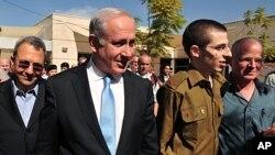 ທ້າວ Gilad Schalit ທະຫານອິສຣາແອລ (ຄົນທີສອງ) ຍ່າງຄຽງ ຂ້າງ ນາຍກົລັດຖະມົນຕີ Benjamin Netanyahu, ທີ່ຖານທັບ ອາກາດແຫ່ງນຶ່ງໃນພາກໃຕ້ຂອງອິສຣາແອລ. ວັນທີ 18 ຕຸລາ 2011.