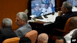 Miguel Diaz-Canel, second left, talks to another person during the start of two-day session of the legislature, in Havana, Cuba, Wednesday, April 18, 2018. Cuba's legislature opened the two-day session that is to elect a successor to President Raul Castro, at right. (AP Photo/Ramon Espinosa)