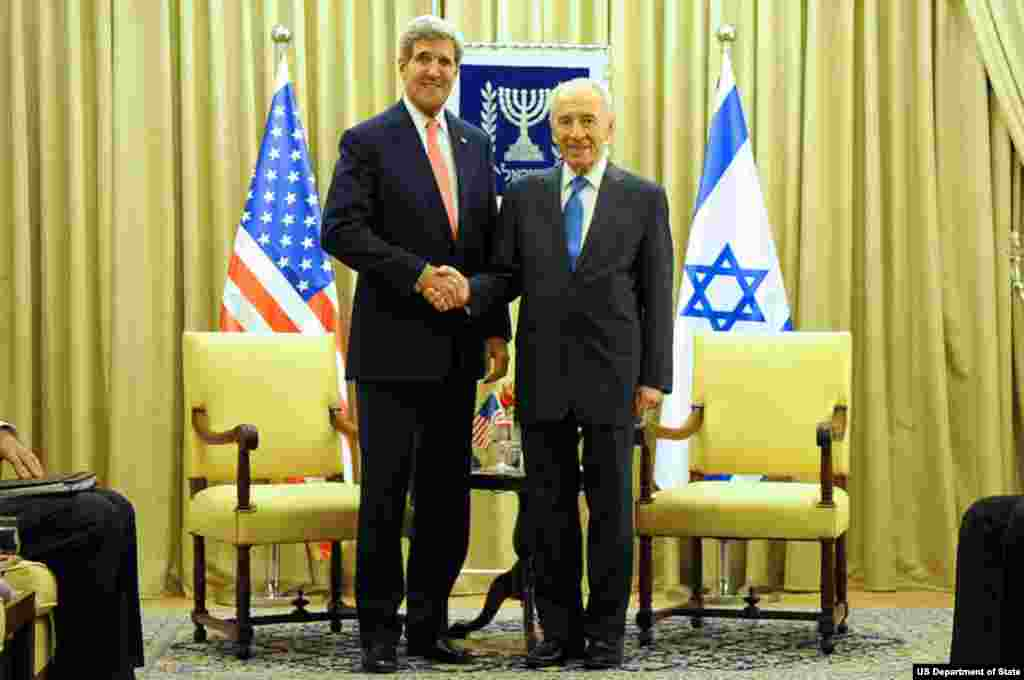 U.S. Secretary of State John Kerry and Israeli President Shimon Peres shake hands for reporters before making statements about Middle East peace at outset of a meeting in Jerusalem on November 6, 2013.