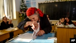 A woman casts her vote in Sintesti, Romania, Dec. 11, 2016.