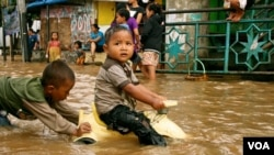 Children play in flood waters after torrential rains in Kampung Melayu, South Jakarta, Indonesia, January 17, 2013. (K. Lamb/VOA)