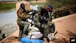 Tentara Mali melakukan pengawasan di sebuah jembatan masuk ke kota Gao (8/2), di mana pembom bunuh diri sempat meledakkan diri di dekat tempat pemeriksaan militer.