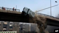 Un vehículo blindado de la policía es empujado fuera del puente 6º de Octubre por los manifestantes.