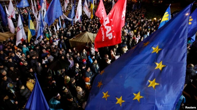 FILE - People attend a meeting to support EU integration at European square in Kyiv, Ukraine, Nov. 25, 2013.
