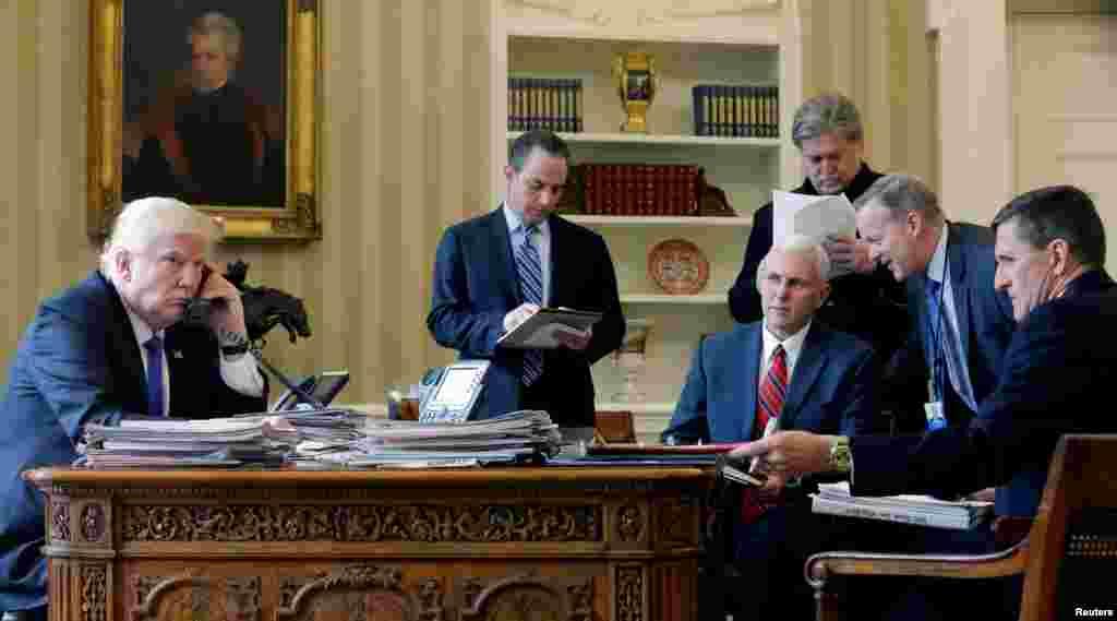 პრეზიდენტი დონალდ ტრამპი ტელეფონით ესაუბრება რუსეთის პრეზიდენტ ვლადიმირ პუტინს. მისი უახლოესი გარემოცვიდან, რომელიც ამ ფოტოზეა, ახლა თანამდებობაზე მხოლოდ ვიცე-პრეზიდენტი მაიკ პენსია დარჩენილი. პოსტები დატოვეს (მარცხნიდან მარჯვნივ): თეთრი სახლის აპარატის უფროსმა რინს პრიბუსმა, უფროსმა მრჩეველმა სტივ ბენონმა, კომუნიკაციების დირექტორმა შონ სპაისერმა და მრჩეველმა ეროვნული უსაფრთხოების საკითხებში, მაიკლ ფლინმა. ამ უკანასკნელს საგანგებო გამოძიებამ ბრალი წაუყენა. 28 იანვარი, 2017 წ.