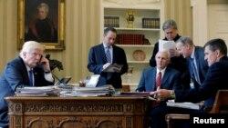 Le président américain Donald Trump avec, de gauche à droite, le chef d'état-major Reince Priebus, le vice-président Mike Pence, le conseiller principal Steve Bannon, le directeur de la communication Sean Spicer et le conseiller à la sécurité nationale Michael Flynn, au téléphone au Bureau ovale à la Maison Blanche, Washington, 28 janvier 2017.