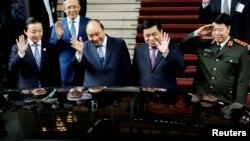 Thủ tướng Việt Nam Nguyễn Xuân Phúc vẫy tay chào tạm biệt Thủ tướng Nhật Bản Suga Yoshihide (trong ô tô) tại Văn phòng Chính phủ ở Hà Nội hôm 19/10. Nhật và Việt Nam đạt được 1 thoả thuận chuyển giao thiết bị quốc phòng trong bối cảnh lo ngại về ảnh hưởng gia tăng của Trung Quốc.