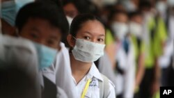 In this photo taken on Jan. 28, 2020, Cambodian students line up to sanitize their hands to avoid the contact of coronavirus before their morning class at a high school in Phnom Penh, Cambodia.
