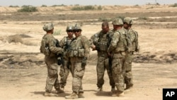 FILE - U.S. soldiers are seen with Iraqi troops, outside Baghdad, Iraq, May 27, 2015.