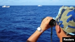 TƯ LIỆU - Cảnh sát biển Việt Nam quan sát hoạt động của một tàu hải cảnh của Trung Quốc gần giàn khoan Hải Dương 981 ở Biển Đông, ngày 15 tháng 7, 2014.