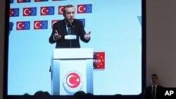 7일 터키 이스탄불에서 레제프 타이이프 에르도안 터키 총리가 연설을 하는 가운데 개인 경호원이 스크린 옆에 서서 지키고 있다.