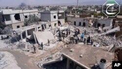 Warga Suriah berkumpul di antara rumah-rumah mereka yang hancur akibat serangan udara pasukan pemerintah Suriah di Qusair, provinsi Homs (Foto: dok).