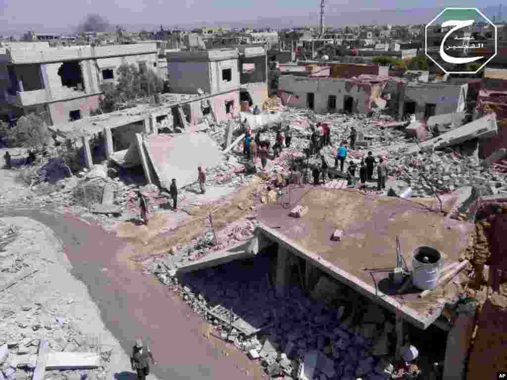 This citizen journalism image provided by Qusair Lens shows people gathered by houses that were destroyed in an airstrike in Qusair, Homs province, Syria, May 21, 2013.