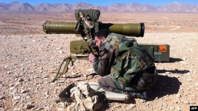 A pro-regime soldier aims a rocket launcher towards rebel locations in the Qalamoun region on the outskirts of the Syrian capital Damascus, Feb. 13, 2014.