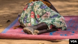 A woman is sleeping outside Yoyo health center, Bidibidi refugee settlement. Many of those able to make the journey and cross the border into Uganda arrive in a worrying state of health after walking for days or weeks, often with no access to food and clean water, requiring immediate medical attention and humanitarian assistance. (N. Jidovanu/VOA)