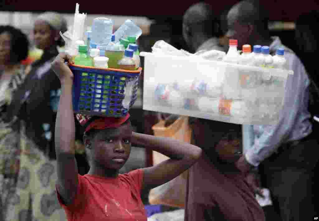11일 나이지리아 라고스의 버스 정거장에서 음료를 파는 소녀.