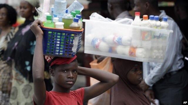 O comércio ambulante é a via por excelência dos adoslecentes nigerianos no seu quotidiano. Esta fotografia retrata uma jovem vendendo água e gasosas na estação de autocarro na cidade de Lagos - Outubro 2012
