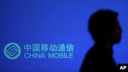 一名男子走過有中國移動標識的廣告牌。