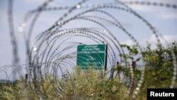 지난 2015년 7월 조지아 국경 지역에 러시아가 붙여놓은 경고문이 철조망 사이로 보인다.