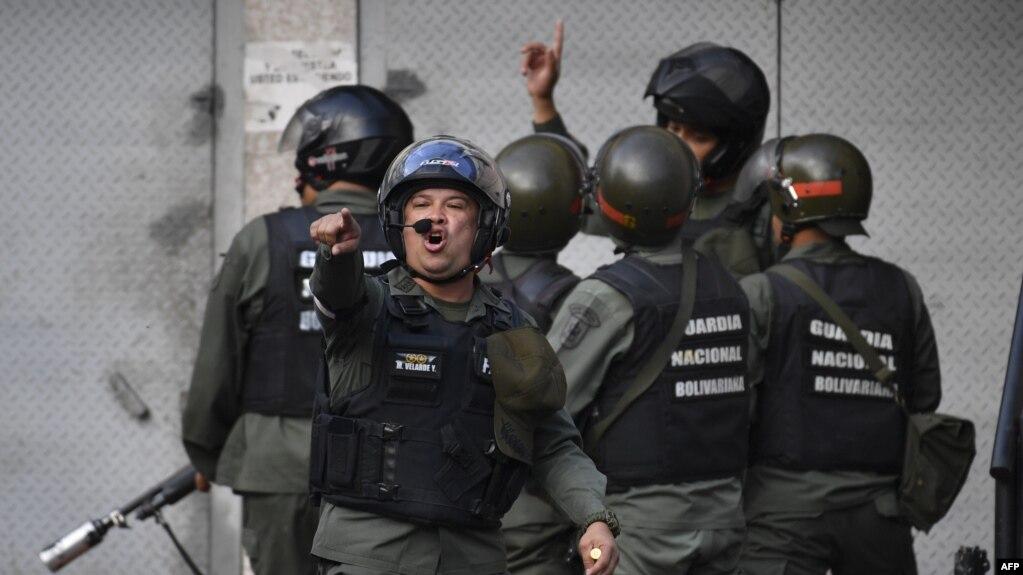Lực lượng an ninh tìm cách giải tán người biểu tình bên ngoài trụ sở của lực lượng Vệ binh Quốc gia hôm 21/1.