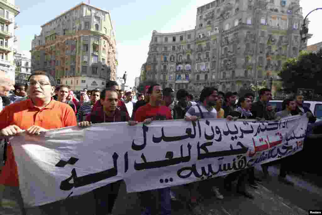 Anti-government protesters shout slogans against a new law in Egypt that restricts demonstrations, in downtown Cairo, Nov. 26, 2013.