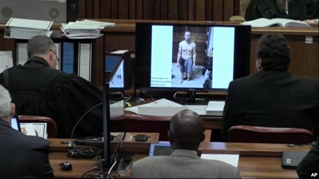 An image taken from the court pool TV via AP showing on screen a police photograph of Oscar Pistorius standing on his blood-stained prosthetic legs and wearing shorts covered in blood, taken shortly after the athlete fatally shot his girlfriend, which was shown to the court in Pretoria, at his murder trial, Mar. 14, 2014.