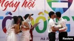 Các cặp vợ chồng đồng tính Lê Thùy Linh và Trần Ngọc Diễm Hằng cùng Hồ Hải Thịnh và Phạm Tiến Dũng hôn nhau tại lễ cưới tại Hà Nội, ngày 27/10/2013.