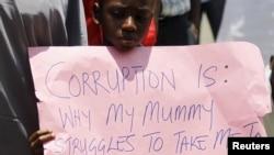 Un garçon tient une pancarte lors d'un rassemblement en soutien à la campagne anti-corruption du président Muhammadu Buhari, à Abuja, au Nigeria, le 17 août 2015.