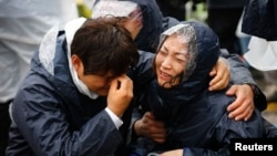Family members of passengers missing on the overturned South Korean ferry Sewol react to the disaster.